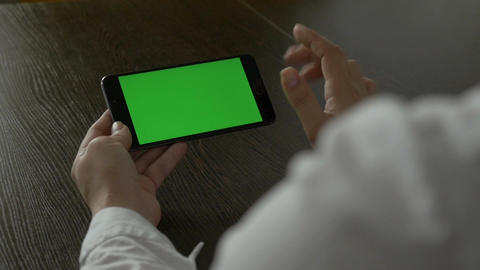 Woman holding a mobile phone with a green screen. For your video content ビデオ