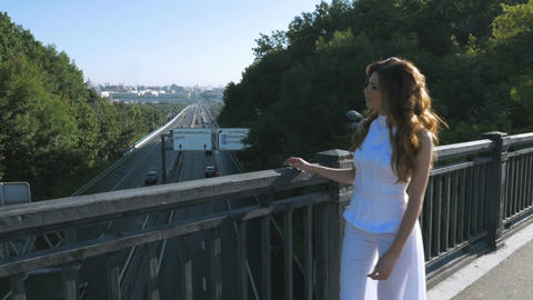 A young woman with long hair walks along the pedestrian bridge. She looks at the Footage