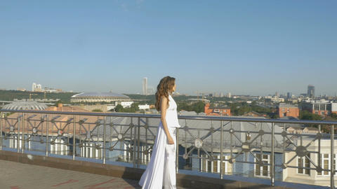 A young woman in white clothes, walking along the tourist observation platform Footage