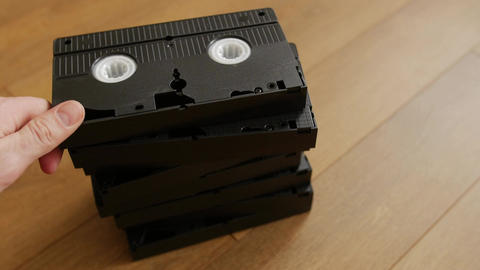 Stack of VHS video tape cassette over wooden background, top view Footage