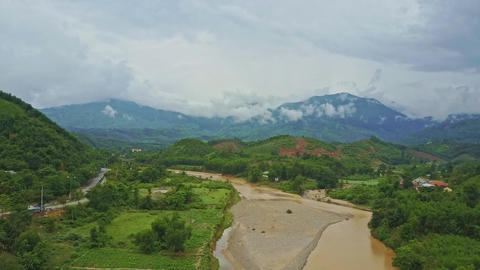 Aerial View River Runs between Green Banks against Mountains Footage