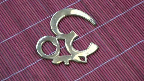 Rotating hindu OM sign brass souvenir on red bamboo mat ビデオ