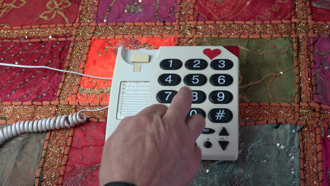 Man pressing numbers buttons on retro telephone on colorful tablecloth Footage