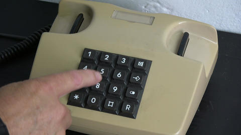 pressing numbers buttons on retro phone telephone on black table Archivo