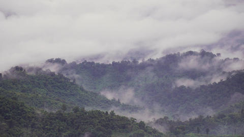clouds moving over green forest mountain in the morning,Rainy season in Thailand Footage