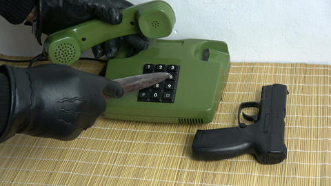 Robber gangster hand with glove and dagger gun pressing buttons on retro green Archivo