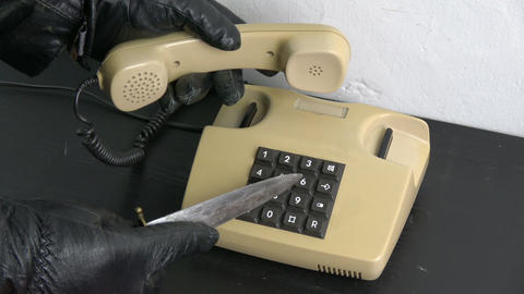 Robber gangster hand with and dagger pressing numbers buttons on old telephone Archivo