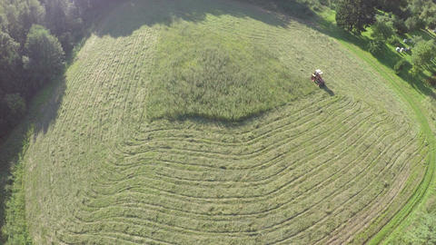 old tractor cut grass from summer meadow in farm, aerial view Archivo