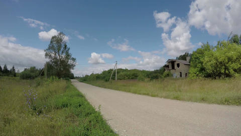 rural gravel road and derelict house ruins. Time lapse Footage
