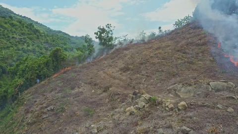 Flycam Approaches Man Extinguishing Fire High in Hilly Jungle Footage