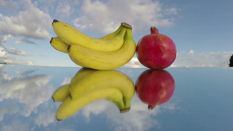 banana and pomegranate fruits on mirror and clouds motion. Time lapse Footage