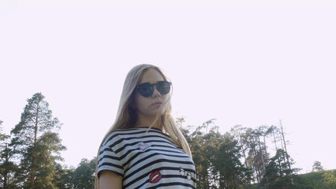 Girl in sunglasses is standing still Live Action