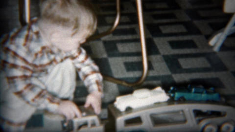 1962: Toddler boy playing with car carrier truck on kitchen floor Footage