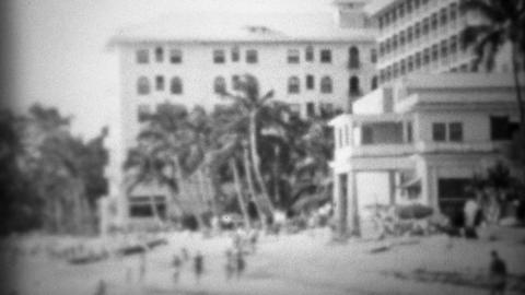 1953: Historic Moana Surfrider beach hotel with tourists frollicking about Footage