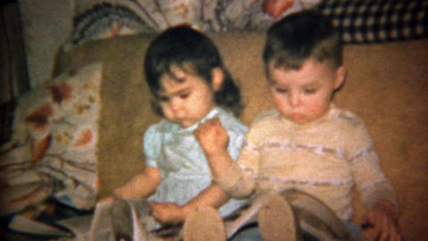 1962: Toddler boy and girl reading magazines on couch Footage