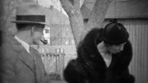 1933: Man smoking pipe wife in black fur coat with funny formal hats Footage