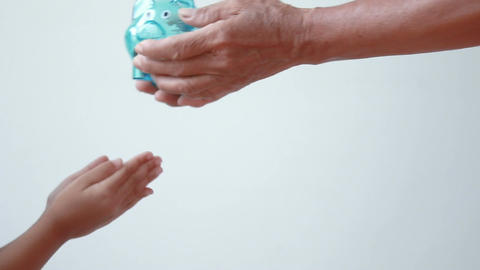 Hands of old woman grandmother giving clear piggy bank to Asian little girl over Footage