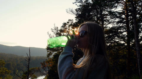 Girl stands high in the mountains and drinks water from a bottle Footage