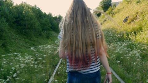 Girl steps forward along the rails Footage