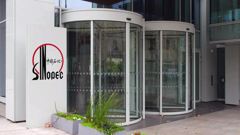 Street signage board with Sinopec logo. Modern office building. Editorial 4K 3D Footage