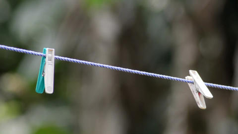 Mid close bokeh shot of two hanging cloth clips on a rope Archivo