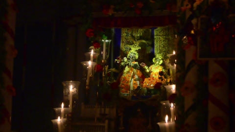 Mid shot of a statue of Lord Krishna and Radha surrounded by beautiful candles Image