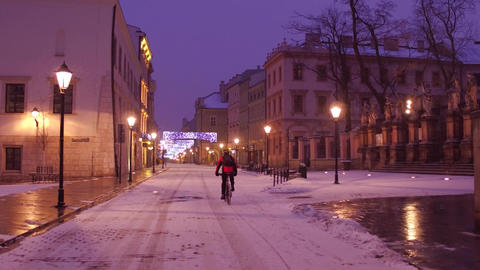 Krakow old town street and lonely biker riding in the snow ビデオ