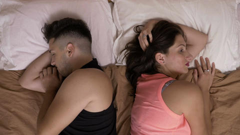Relationship problems with young couple lovers in bed standing back to back Live Action