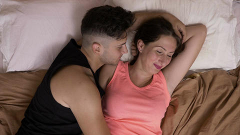 Couple with young man laying in bed next to his girlfriend comforting and Footage