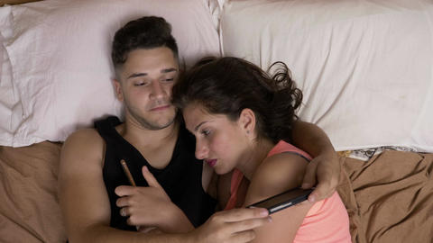 Couple addicted to social media networks spending time in bed together hugging Footage