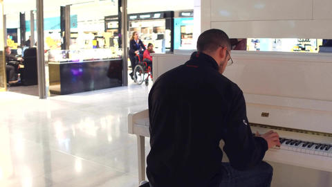 PARIS, FRANCE - JANUARY, 1, 2017 Steadicam shot man playing piano in duty free Footage