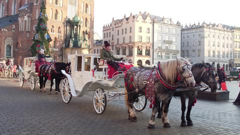 KRAKOW, POLAND - JANUARY, 14, 2017 Horse drawn carriages and Christmas decorated Foto