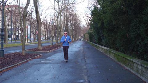 VIENNA, AUSTRIA - DECEMBER, 25 Senior male runner on city sidewalk Fotografía