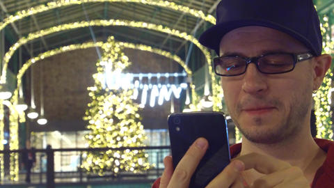 Happy man in black rim glasses scrolls app in his mobile phone in a Christmas Footage