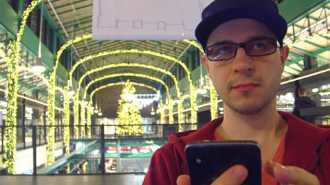 Man in black rim glasses typing message on his mobile phone in a Christmas Footage