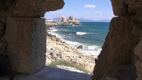 Rhodes old town port and Aegean sea from castle fort ruins window hole, Greece Footage