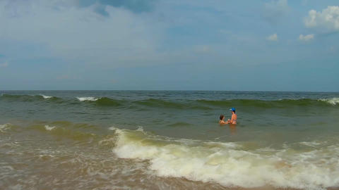 Mom and daughter swim in the ocean splashing Archivo