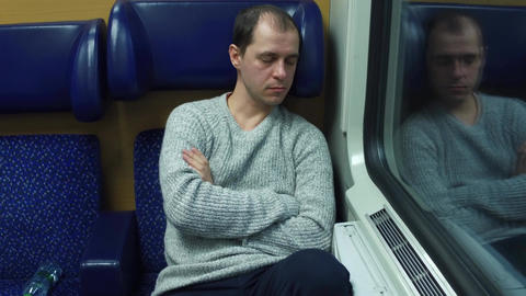 Tired man in sweater sleeping in his seat in a train Footage