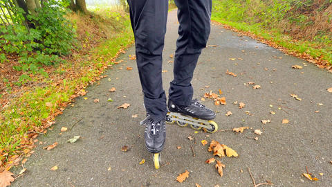 Outdoor inline skating on wet slippery asphalt in autumnal forest. Man legs in Archivo