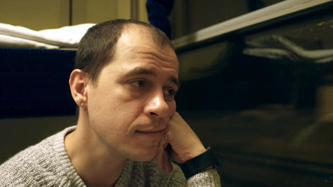 Thoughtful man with earring travelling by train at night Footage