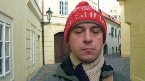Sad man in red knitted hat walking on a narrow old town street in Prague Footage