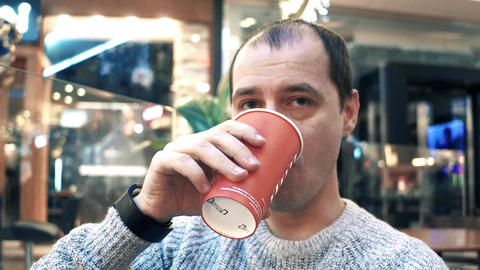 Thoughtful man having big disposable paper cup of coffee in a cafe Footage
