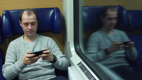 Man playing game in his smartphone in a train Footage