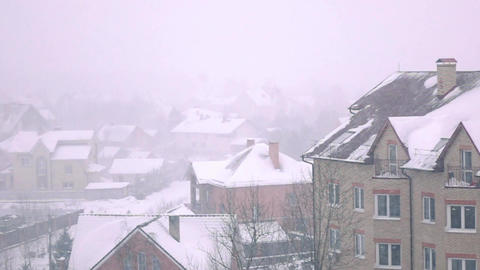 Snowstorm above sloped roofs of residential houses in winter Footage