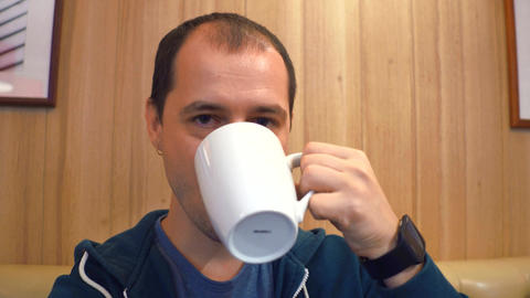 Serious young man having big cup of coffee to keep him awake Footage
