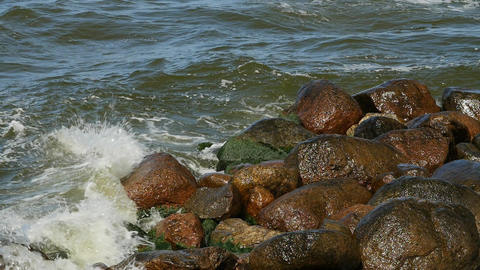 Waves breaks about rocks on the sea. Small waves and round stones Footage