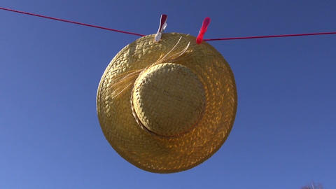 laundry clothes line with woman straw hat in wind Live Action