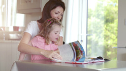 Mother and daughter reading magazine Live Action