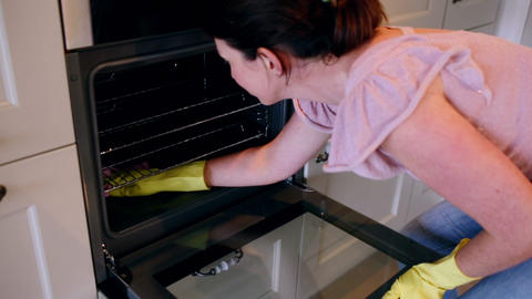 Woman cleaning the oven Footage