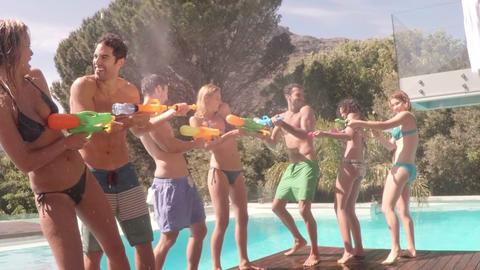 Happy friends doing water gun battle Footage